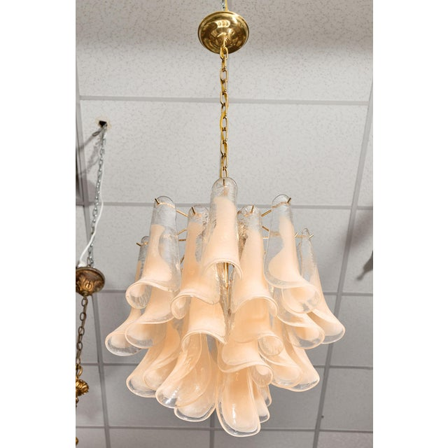 """Pair of peach Murano glass """"selle"""" chandeliers with vintage hand-blown glass. Each glass component features both clear and..."""