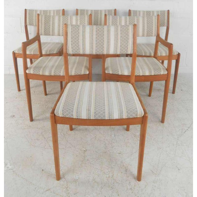 This set of six mid-century dining chairs features beautiful teak frames with upholstered seats/backs and traditional...