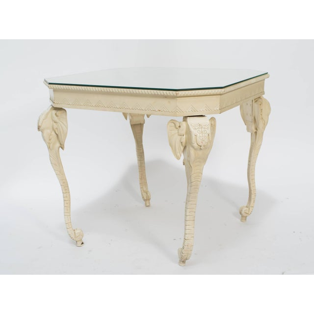 Carved and painted elephant leg occasional table with glass top.
