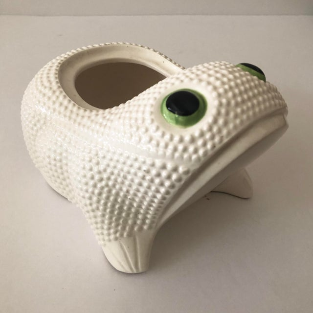 Vintage ceramic frog planter with hobnail exterior and green eyes.