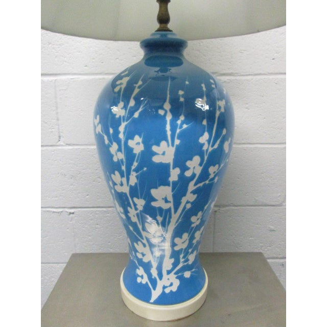 """Pair of blue ceramic floral lamps. Measures: 33"""" H (top of finial) and 22"""" H (under bulb socket). 9.25"""" W (at it's..."""