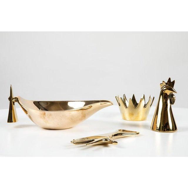 Set of four Carl Auböck brass objects. Includes Carl Auböck model #4072/G 'Rooster' brass bell, model #3600 'Crown'...