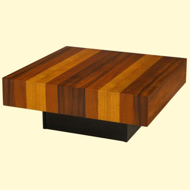 Dyrlund of Denmark parquetry wood square form coffee table with black lacquered recessed wood base. Clad in several exotic...