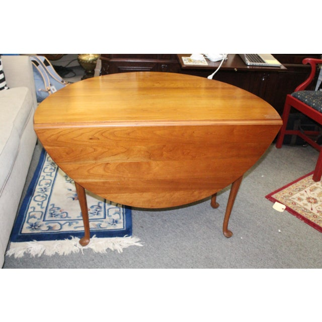 "Cherry drop leaf table on four sturdy legs. The leaves open up to reveal a circular table, 46"" in diameter."