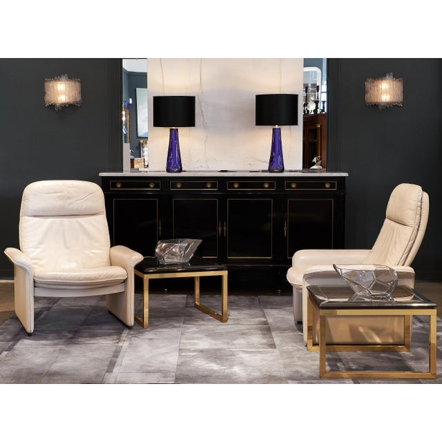 A French pair of side tables made of gilt brass with an ebonized wood top framing the original smoked glass top. The wood...