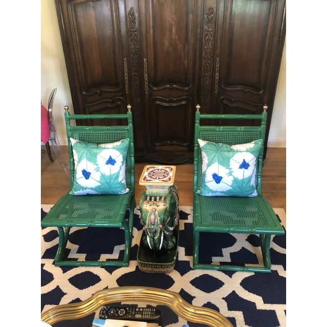 A pair of faux bamboo cane Campeche chairs. These are unique chairs with a green high gloss paint. The caning is all intact.