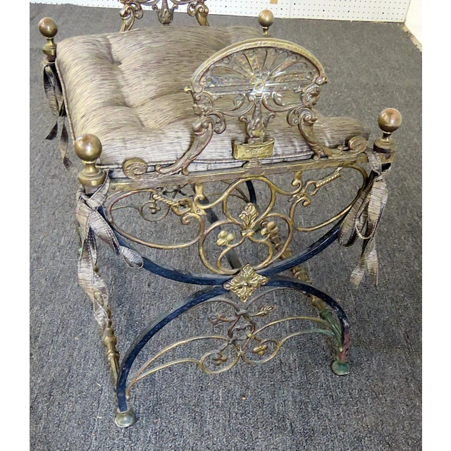 Antique Regency style iron bench with cushion. The piece dates back to the late 19th century.