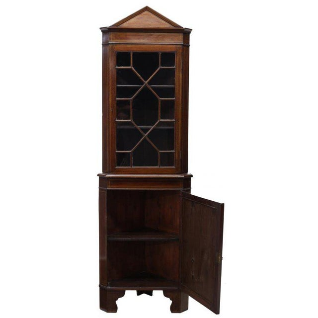 This Danish inlaid mahogany corner cupboard was made in the 19th c. It features a pediment top over a glass paneled door,...