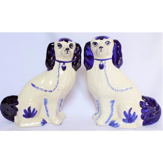 This is a whimsical pair of blue and white Staffordshire dog statues. These are very fun and are in a creamy white ceramic...