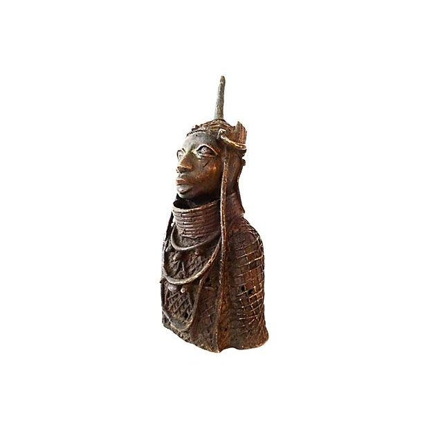 "Cast bronze King Oba figure wearing a ceremonial garment, headdress, and collar. Minor holes from the cast 4"" L x 5.5"" W x..."
