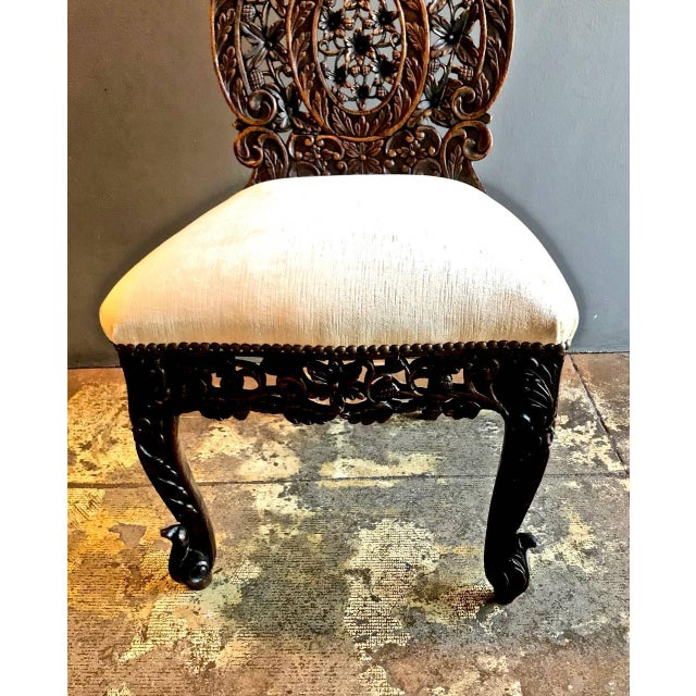 This is a intricately carved sculptural rosewood Anglo-Indian side chair that has been newly upholstered in a very light...