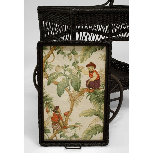 American Victorian black painted wicker bar cart with two large front wheels supporting a shelf with gallery and a tray...