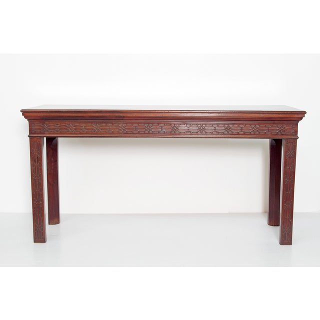A George III mahogany side table with later mahogany top, Chinese Chippendale fretwork, carved frieze on conforming blind...