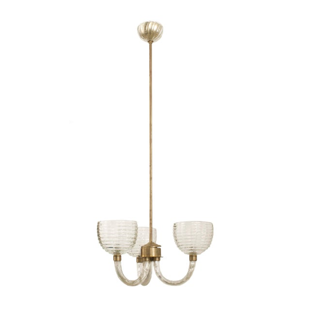 Italian 1930s clear fluted glass three-arm chandelier supporting large tiered beehive shaped shades emanating from a brass...