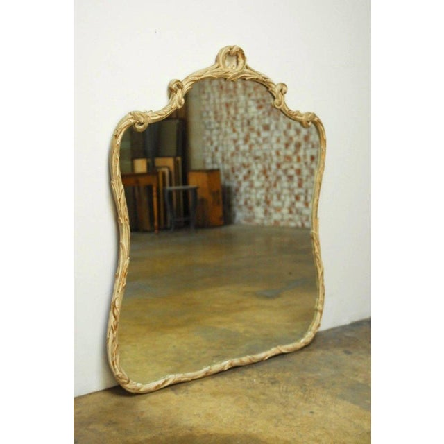 Elegant Italian Rococo style painted gilt wood mirror featuring a hand-carved laurel leaf, foliate design. The frame has a...