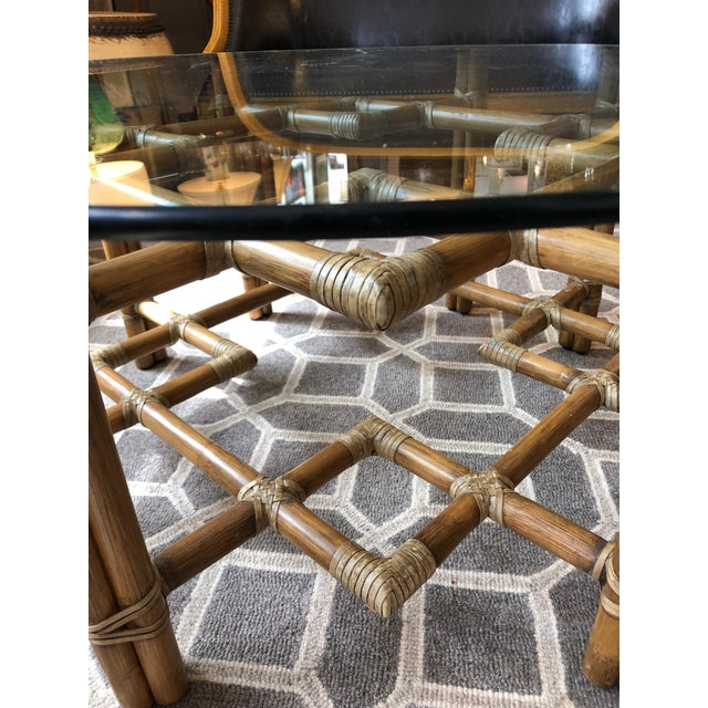 Super stylish round rattan coffee table having geometrically layered rods of rattan with raffia rope like wrapping and...