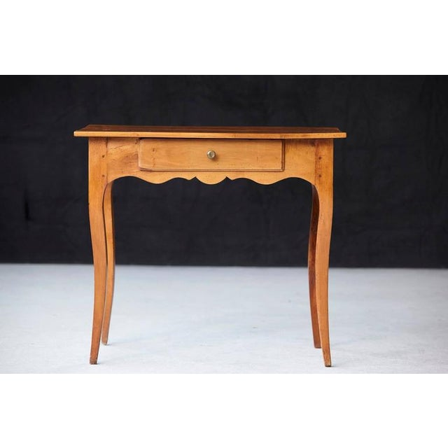 Charming French Provincial fruitwood occasional table, circa 1890, featuring a single drawer, shaped apron and raised on...