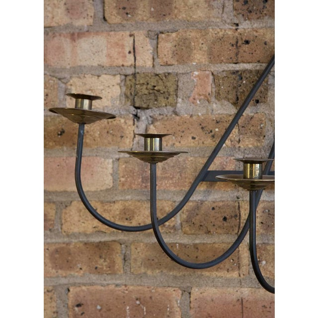A fantastic 1950's Iron Wall Sconce with 7 arms; made of iron and featuring brass bobeche on each. Sculptural, modern and...