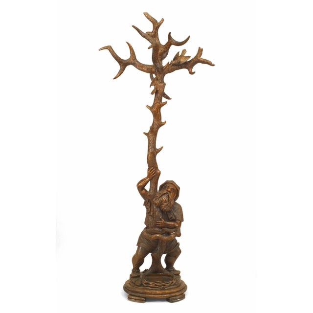Rustic black forest 19th century carved walnut hatrack or umbrella stand with gnome figure holding tree form with birds in...