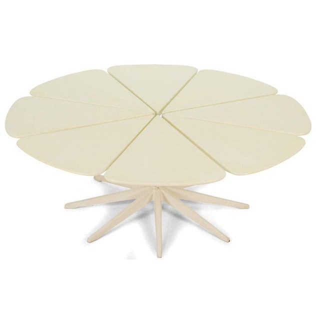 """A mod coffee table with a round top comprised of eight redwood """"petals"""" resting atop a metal pedestal base with eight..."""