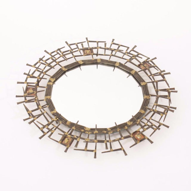 Circa 1970 mixed-metal brutalist style round mirror in the manner of Silas Seandel. Composed of nails, welded copper and...