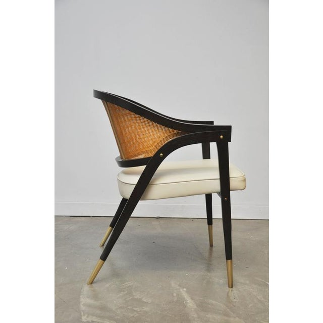 Captain armchair designed by Edward Wormley for Dunbar. Sculptural form wood frame with brass details. Cane back, new...