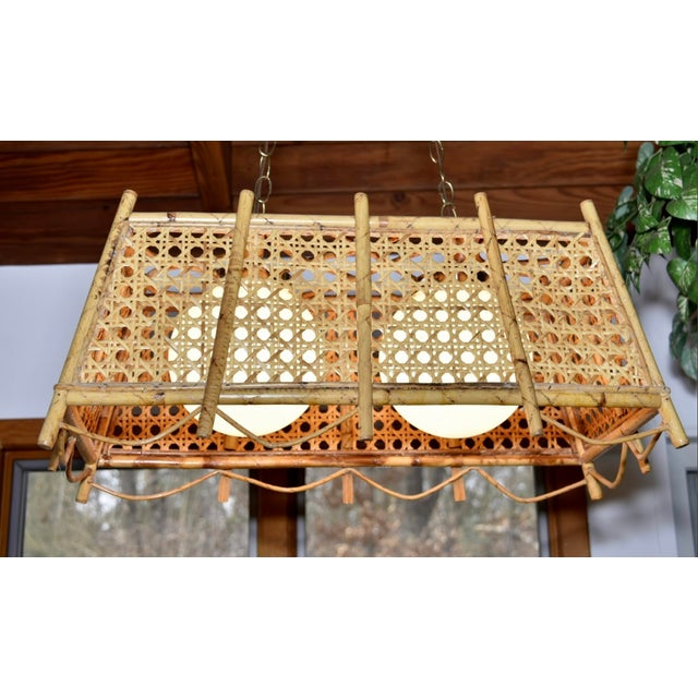 Large rectangular rattan with caned insets vintage chandelier. Sides flare out. Scalloped rattan detail on the bottom -...