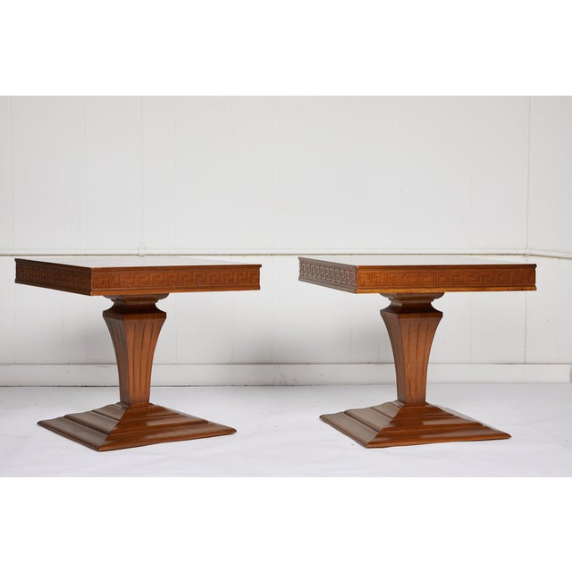 Mid Century pair of low square side or end tables with a checkered veneer top and Greek key apron over a carved urn shaped...