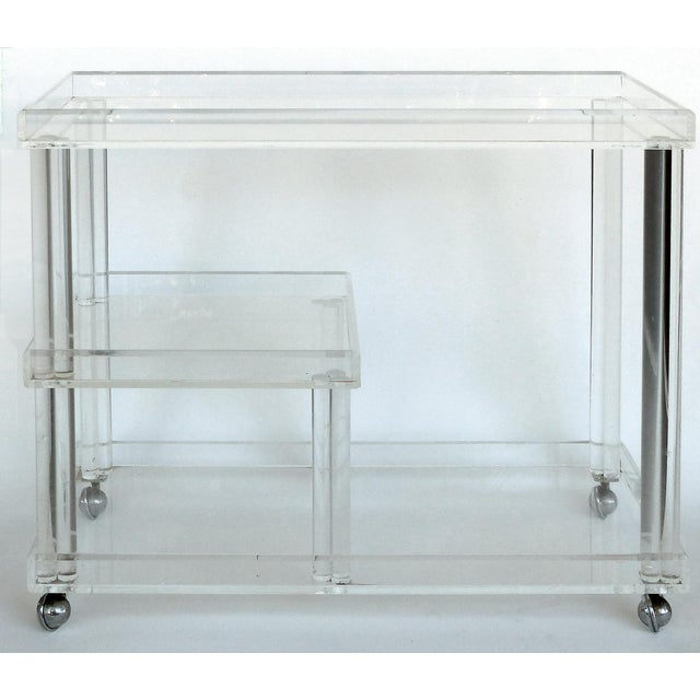 Offered for sale is a Mid-century Modern rolling Lucite Bar Cart. The cart has different levels for storage and serving...