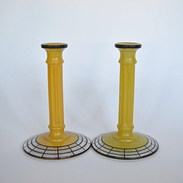 A pair of cast glass Art Deco candlesticks with neoclassical influence. Painted enameled yellow surface shows some wear,...