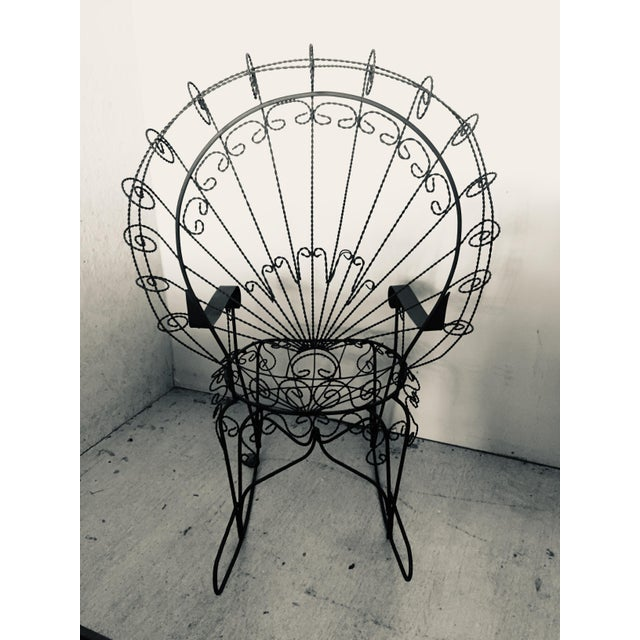 Mid-Century wrought iron rocking chair with lacy wire work, and a black wrought iron frame resembling a peacock's fanned...