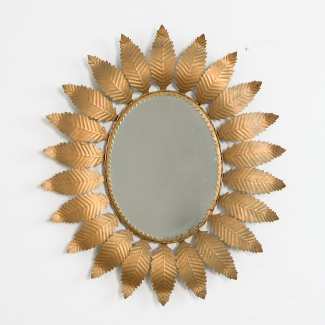 From Spain circa 1960, an oval mirror framed by beaten metal leaves. With a rose gold tinted finish. A typical 1960s...