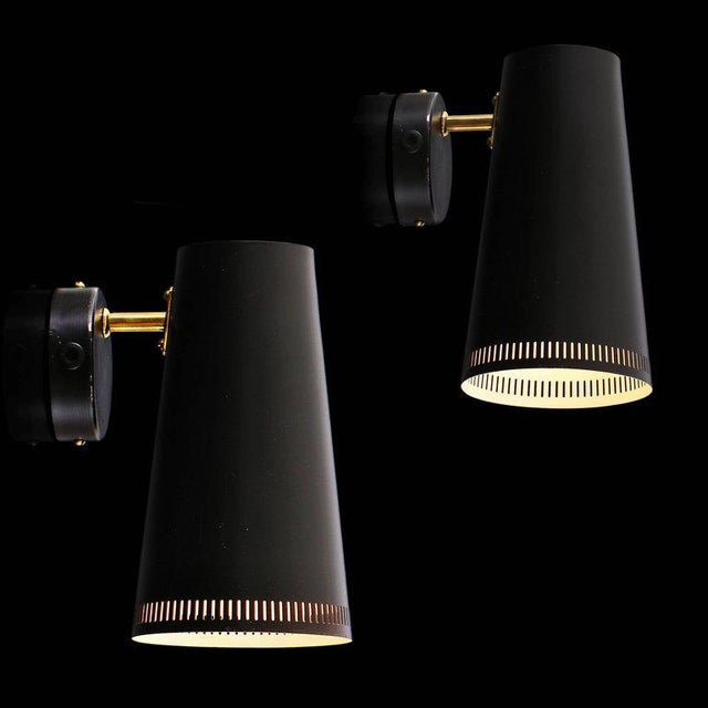 Large pair of Paavo Tynell black wall lights for Taito Oy. Executed in black painted metal and brass. A highly adjustable...