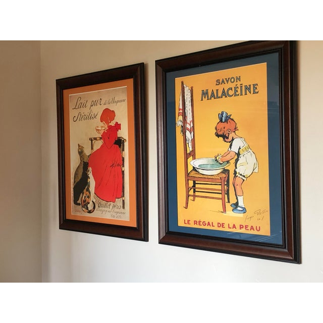 A charming print of French soap advertisement custom framed with a navy blue mat, warm walnut wood and covered in UV...