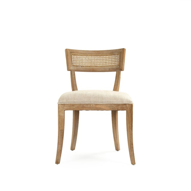 Curved cane back side chair upholstered in natural cream linen on limed grey oak legs.