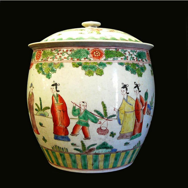 This is a handmade porcelain pot with lid. The surface is painted with a color graphic of oriental people gathering...