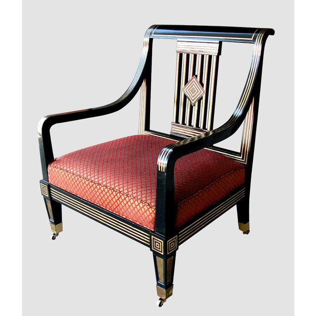 An impressive and boldly scaled Russian neoclassical style black lacquer armchair with brass inlay; the outwardly...