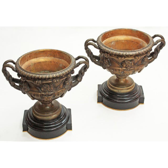 a pair of cast bronze Grand Tour urns / Warwick Cups with classical busts in high relief on body, entwined handles, the...
