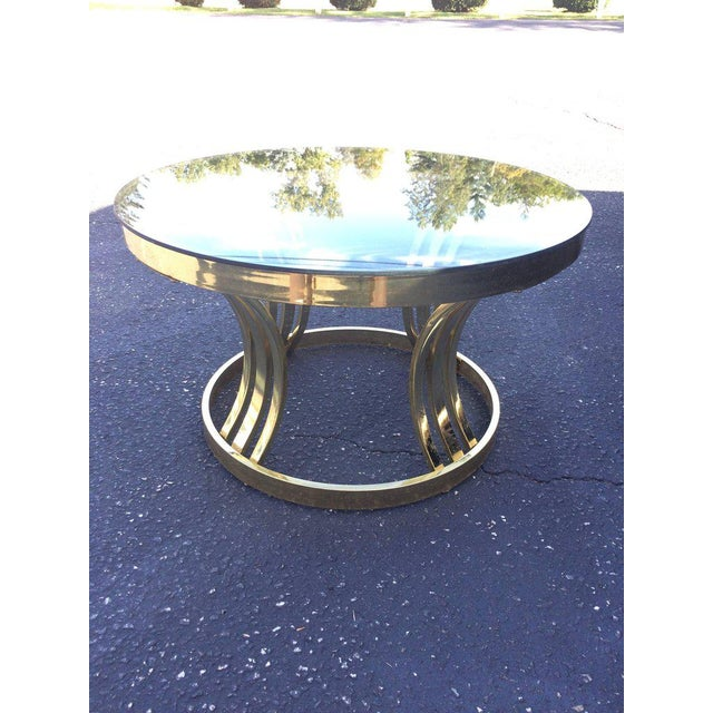 Mid-Century brass and smoked glass round coffee table by Milo Baughman. Nice size to this sleek table. Some wear to brass...
