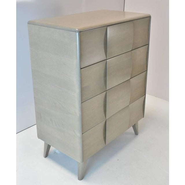 A Mid-Century Modern four-drawer chest with sculptural block front and shaped legs. Refinished in a silver grey stain.