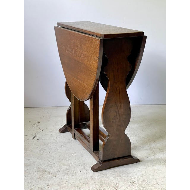 19th Century English solid oak trestle table with nicely shaped plank ends and gatelegs on either side that support...