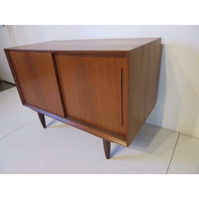 A smaller scale teak wood credenza with double sliding doors and one adjustable shelve sitting on conical legs . Made in...