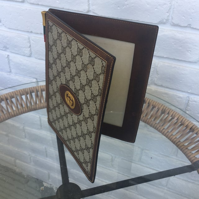 A Vintage folding picture frame by Gucci. No rips or tears but spotting to leather from age. Beautifully hinged with a...