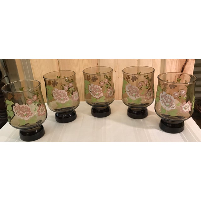 Really nice set of five smokey glass footed glasses with a floral design that is embossed on the outside of the glass. The...