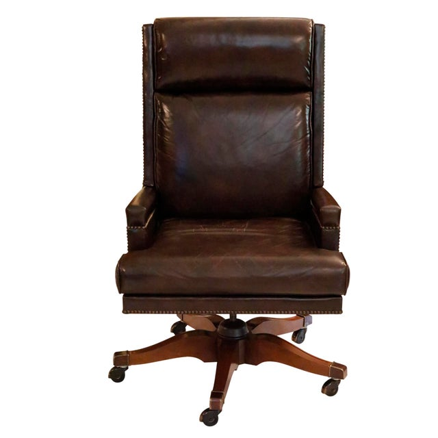 An executive leather desk chair made by Baker Furniture. Brown leather is secured with brass nail heads over a square...