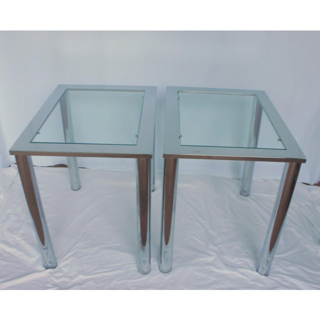 A pair of Milo Baughman style chrome and glass insert side tables. Tubular chrome column legs and glass top flush with the...