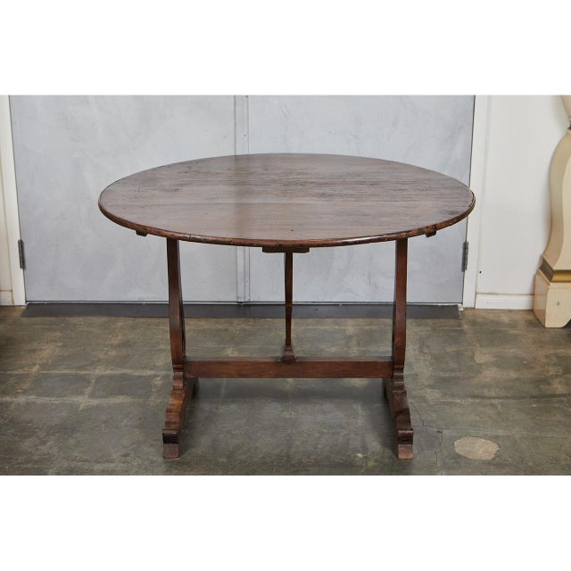 This large French wine table has a round, flip top with shaped supports and legs and two standing feet. This table's...