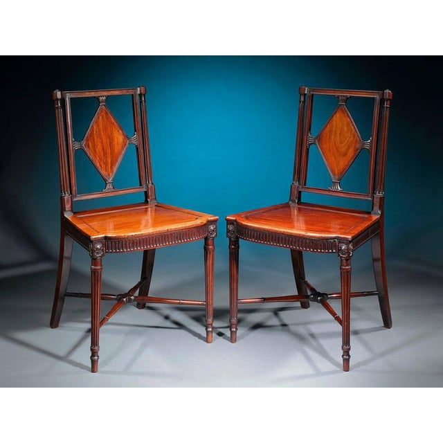 A fine pair of George III era mahogany hall chairs of exceptional craftsmanship and condition. Each masterfully carved...