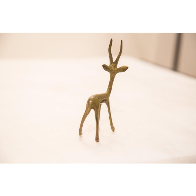 Vintage handmade bronze African sculpture of a gazelle with slight green patina. Circa mid 20th century and possibly...
