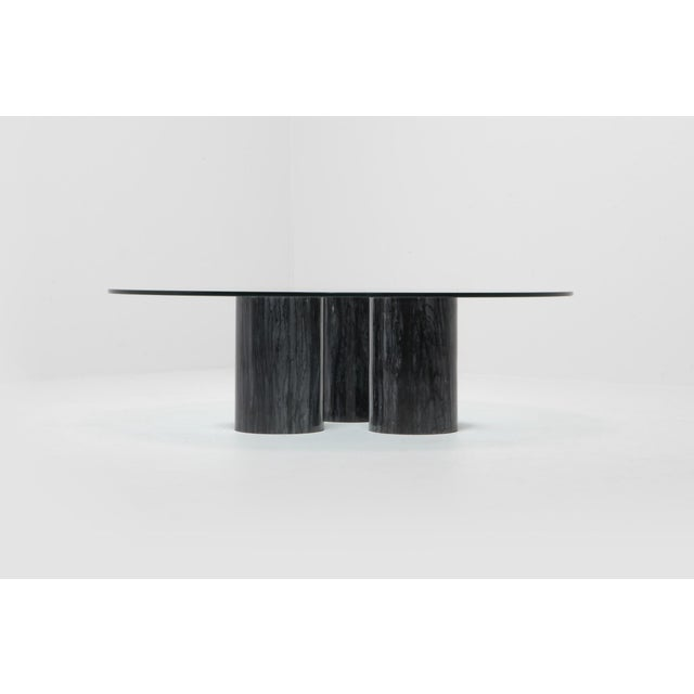 Post-modern cocktail table by Mario Bellini Three black marble columns support a round glass top. As the marble columns...